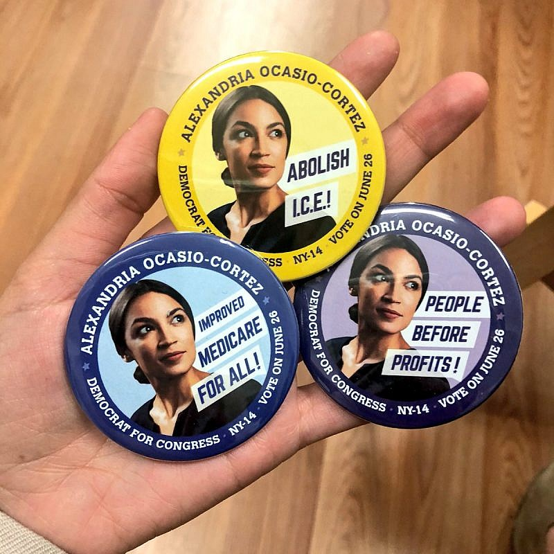 Campaign buttons for Alexandria Ocasio-Cortez, a Democratic Socialist who led a surprise upset victory over Rep. Joe Crowley (D-N.Y.) in a Democratic Party primary on June 27. Credit: Twitter.