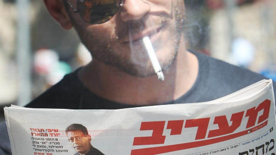 Israelis read about raised taxes on cigarettes and beer back on July 26, 2012. Photo by Miriam Alster/Flash90.
