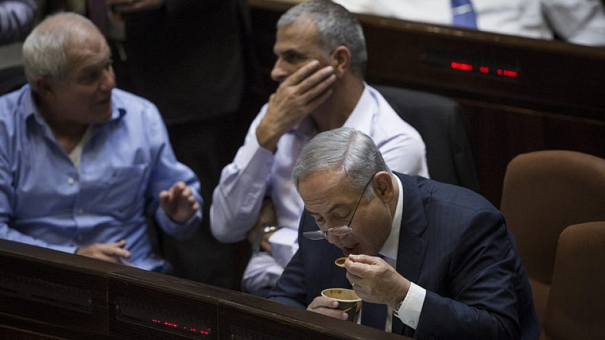 Israeli Prime Minister Benjamin Netanyahu seen eating soup during late-night votes at the assembly hall of the Israeli parliament on November 18, 2015, during the state budget vote for 2015-16. Photo by Hadas Parush/Flash90.