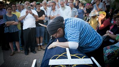 The mother of Hallel Yaffa Ariel and family members mourn over her body during her funeral ceremony in the Jewish settlement of Kiryat Arba in the West Bank on June 30, 2016. Photo by Yonatan Sindel/Flash90.