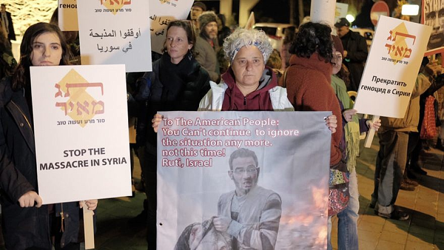 Protesters hold signs during a call to end the war in Syria near the Russian Embassy in Tel Aviv on Dec. 18, 2016. Photo by Tomer Neuberg/Flash90.