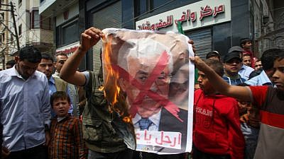 Palestinians burn a crossed poster depicting Palestinian Authority leader Mahmoud Abbas in Khan Younis in southern Gaza on April 14, 2017. Photo by Abed Rahim Khatib/Flash90.