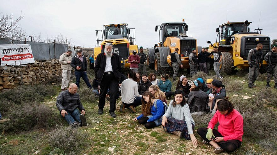 Civil Administration representatives and Israelii Border Police arrive with tractors to begin preparations for evacuation and demolition of the illegal Jewish neighborhood of Netiv Ha'avot, as Jewish settlers block their way, Feb. 6, 2018. Photo by Gershon Elinson/Flash90.