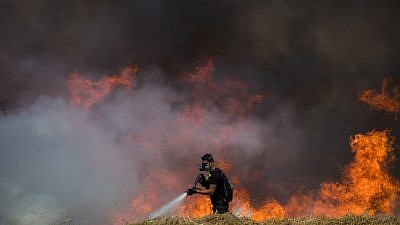 Israeli firefighters extinguish flames in a wheat field caused from kites flown by Palestinian protesters near the border with Gaza on May 30, 2018. Photo by Yonatan Sindel/Flash90.