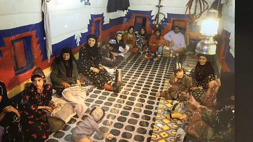 A Yemenite Jewish family in the multifunction room of their home, which would be used for sleeping, eating and entertaining. Photo from a 2018 exhibit in New York City. Credit: Shiryn Solny/JNS.