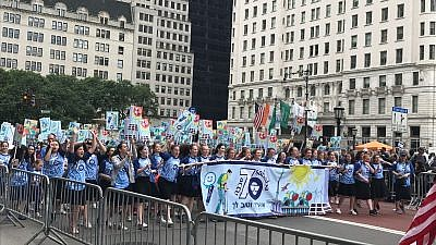 A large group of Jewish teenagers celebrating Israel's 70th anniversary with a banner featuring Israel's ReWalk, a bionic walking assistance system. Credit: Shiryn Solny.