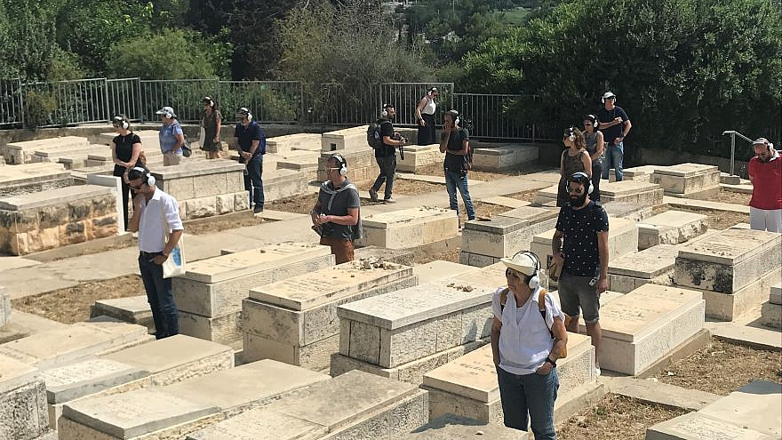 "Participants take part in ""Remote X"" in a Jerusalem cemetery. The tour is based on a skeleton of a narrative in which the performers are ""remoted"" from the normal ways they interact with the city, experiencing it as a meta-reflection while walking the streets. Credit: Eliana Rudee."