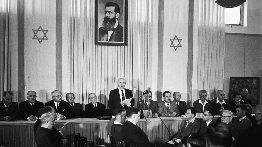 Israeli founding father and first prime minister David Ben-Gurion declares independence beneath a large portrait of Theodor Herzl, founder of modern Zionism. Credit: Wikimedia Commons.