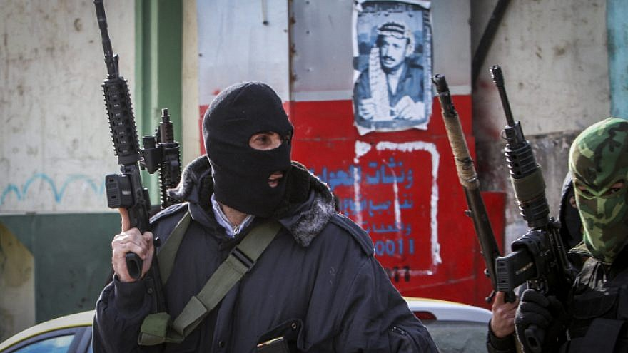 Masked Palestinian militants from the Al-Aqsa Martyrs Brigade, an armed wing linked to Fatah, hold up weapons near Nablus, Jan. 10, 2017.  Photo by Nasser Ishtayeh/Flash90.