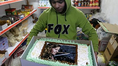 A Palestinian boy holds a cake with a picture of Ahed Tamimi during a protest rally in the city of Hebron on Jan. 30, 2018. Photo by Wisam Hashlamoun/Flash90.