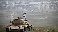 An old Israeli tank with a flag overlooking the Syrian town of Quneitra in the Golan Heights on Feb. 11, 2018. Israeli Air Force F-16 jets were sent to Syria following an invasion of an Iranian drone. Photo by Hadas Parush/Flash90.