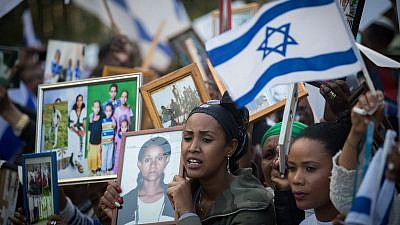 Israelis who immigrated from Ethiopia hold up family photos of loved ones who remain in Ethiopia during a protest to bring the rest of the Falash Mura in Jerusalem, on March 12, 2018. Credit: Yonatan Sindel/Flash90.