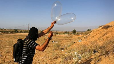 Palestinians in Gaza attach a balloon to flammable materials to be flown towards Israel. These incendiary devices have caused destruction to trees, animals, the land and the environment. June 17, 2018. Photo by Abed Rahim Khatib/Flash90.