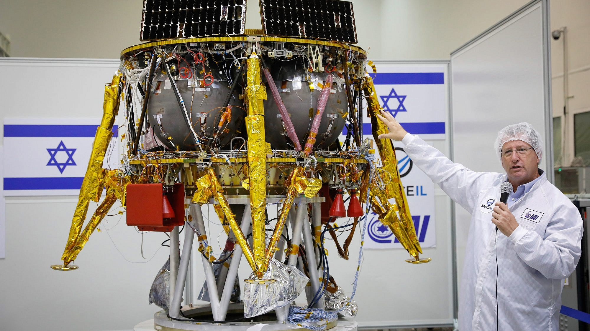 Ofer Doron head of IAI's MBT Space Division speaks near the Israeli spacecraft of the SpaceIL team's spacecraft during a press conference at the Israel Aerospace facility in Yahud