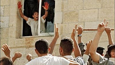 Aziz Salha, one of the participants in the infamous 2000 lynching in Ramallah of two IDF reservists, holds up his blood-stained hands. Salha was released in 2011 as part of the Gilad Shalit prisoner exchange deal. (PMW)