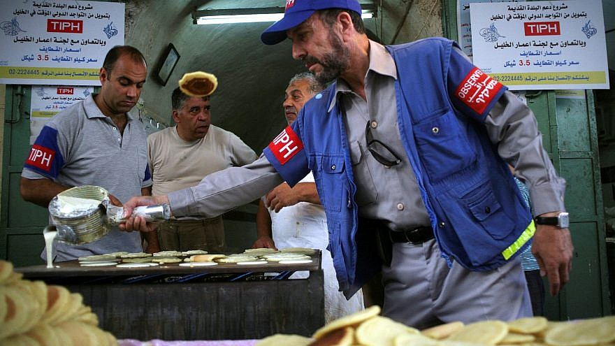 An international observer assists Palestinian shop owners in the old city of Hebron while preparing Ramadan sweets, Aug. 12, 2010. Photo by Najeh Hashlamoun/Flash90.