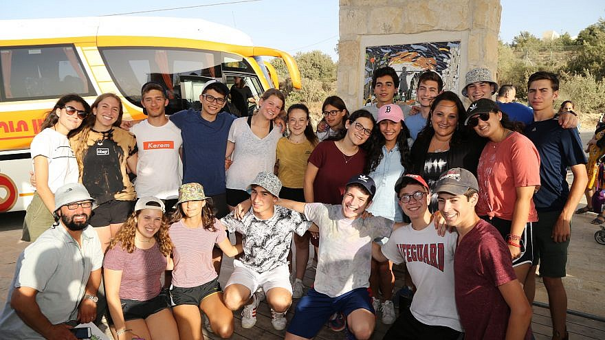 "Ruth Schwartz (second from right, middle row), the mother of Ezra Schwartz, stands at the ""Ezra Schwartz Lookout,"" surrounded by teens in Israel from Camp Yavneh, where her son went to summer camp. Credit: Photo by Gershon Alanson."