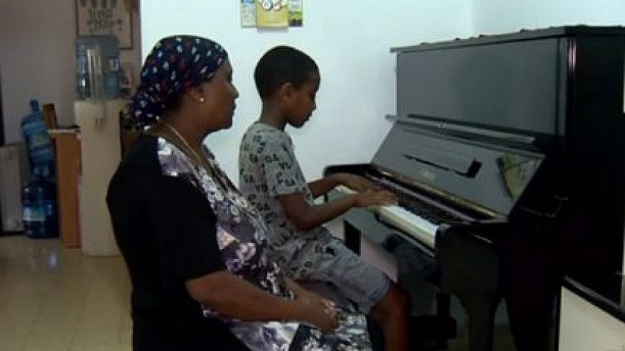 Oshri Bitau with his mother and their new piano. Photo: Hadashot news.