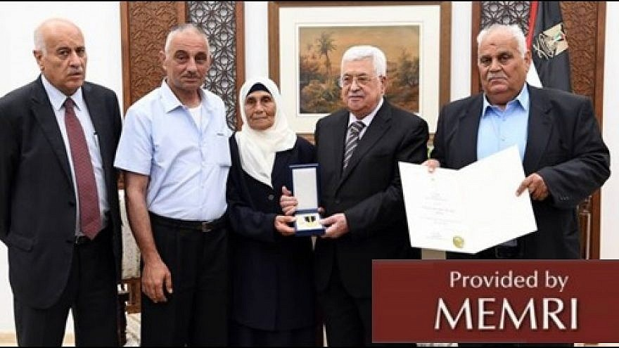 """Palestinian Authority leader Mahmoud Abbas confers a medal on the family of a """"martyred prisoner."""" (Source Pnn.ps, July 23, 2018: MEMRI)"""