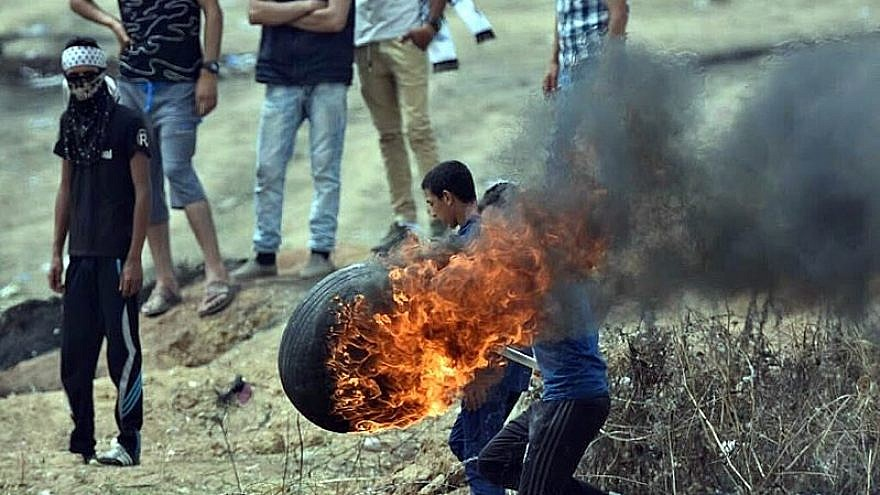 Palestinians burn tires to throw over the Gaza border into Israel on May 4, 2018, as part of weekly riots led by Hamas since March 30. Credit: Wikimedia Commons.