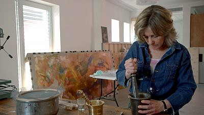 "Beverly Barkat grinds material into fragments with a pestle and mortar for her artwork ""After the Tribes,"" to be exhibited in Rome. Credit: Photo by Tor Ben Mayor."