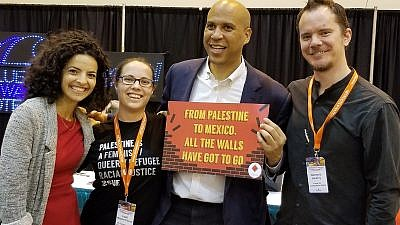 "U.S. Sen. Cory Booker (D-N.J.) holds a sign reading: ""From Palestine to Mexico, all the walls have got to go."" Credit: Twitter via U.S. Campaign for Palestinian Rights."