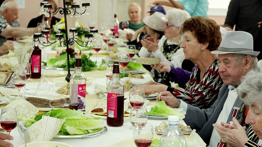 """Senior citizens enjoy a meal for the upcoming Jewish holiday of Passover, organized by the """"Keren Leyedidut""""(International Fellowship of Christians and Jews) organization, in the southern Israeli town of Sderot. April 10, 2014. Photo by Edi Israel/Flash90."""