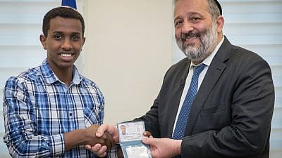 Sintayehu Shafrao from Ethiopia (left), who is competing in the annual International Bible Quiz in Israel, receives a National ID from Israel Minister of Interior Affairs Aryeh Deri during a ceremony at the Interior ministry office in Jerusalem on April 16, 2018. Photo by Yonatan Sindel/Flash90.