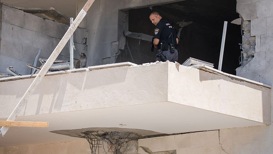 An Israeli police officer examines where a mortar shell from Gaza hit a construction site in the southern Israeli city of Sderot, near the border with Gaza on Aug. 9, 2018. Photo by Yonatan Sindel/Flash90.