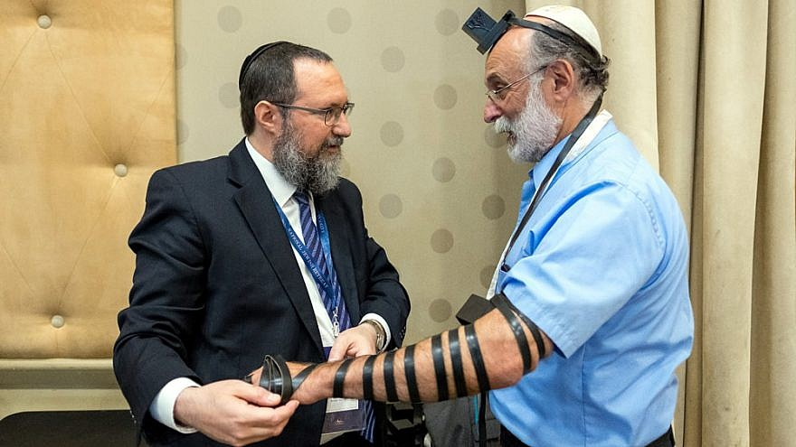 Rabbi Ephraim Mintz, director of the Rohr Jewish Learning Institute, wraps tefillin with Robert Meeropol, 71, the son of convicted and executed U.S. spies Julius and Ethel Rosenberg. Credit: Photo by Mendy Moskowitz/JLI.