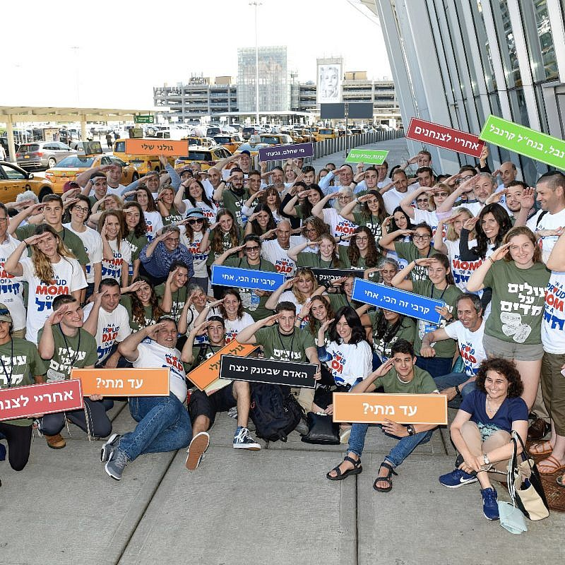 A group of soon-to-be volunteers in the Israel Defense Forces gather outside of John F. Kennedy Airport in New York and salute their future. Credit: Shahar Azram.