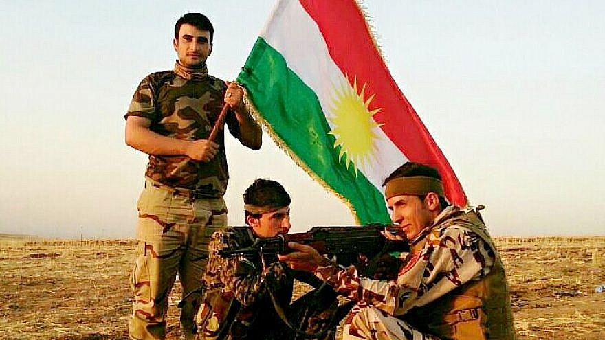 Kurdish Peshmerga fighters display their flag. Credit: Flickr.