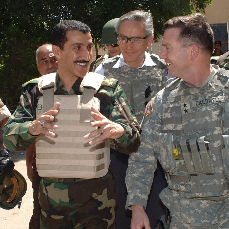 U.S. Army Maj. Gen. William Caldwell (right), chief spokesman for Multi-National Forces in Iraq, walks to the local marketplace with the Iraqi commander of 1st Brigade, 9th Iraqi Army Division in the Zafaraniyah area of East Baghdad, Iraq, April 5, 2007. U.S. Army photo by Staff Sgt. Bronco Suzuki/Wikimedia Commons.