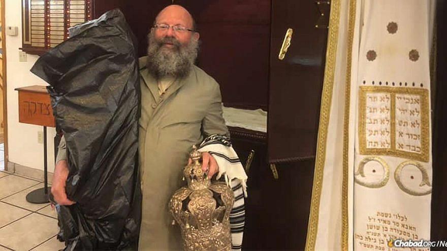 Rabbi Doron Aizenman evacuates Torah scrolls from the Myrtle Beach Chabad synagogue. Credit: Chabad.org/News.