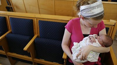 A young mother comforts her baby boy after a brit milah has been performed in a synagogue in Jerusalem on Aug. 30, 2013. Photo by Nati Shohat/Flash90.