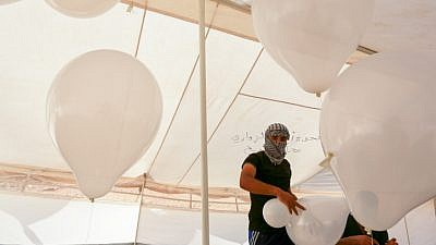 Palestinians prepare balloons that will be attached to flammable material during clashes with Israeli security forces on the Gaza-Israeli border on Aug. 10, 2018. Photo by Abed Rahim Khatib/Flash90.