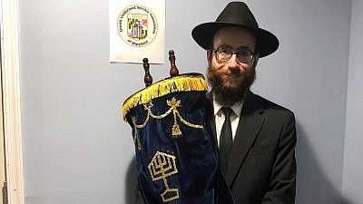 """Chabad Rabbi Yechezkiel (""""Chesky"""") Tenenbaum, chaplain of the Maryland Defense Force, which is part of the Maryland Military Department. He holds a newly refurbished Torah on loan that was named after a Jewish American soldier who served in Afghanistan. Credit: Courtesy."""