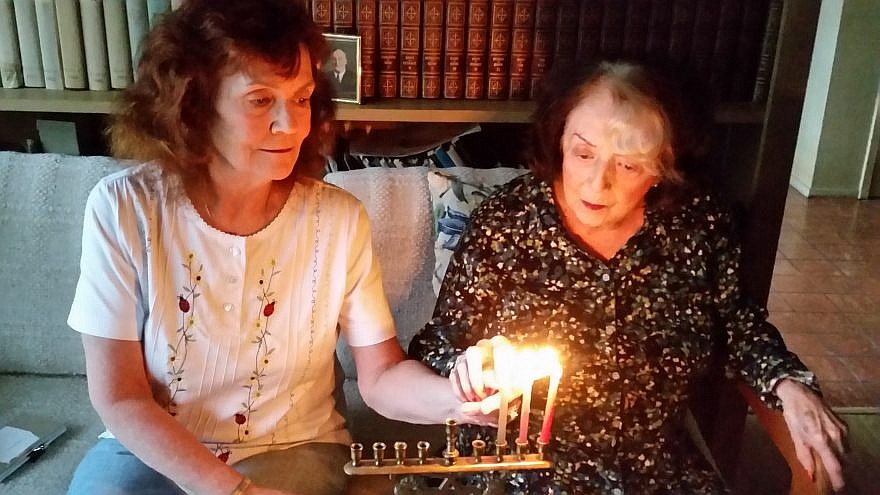 Margery B. Sterns (right), 96, a a longtime resident of San Francisco, lights the menorah with her daughter Sandra. Margery recalls her Russian immigrant parents lighting the menorah as one of her top memories of Hanukkah. Credit: Courtesy.
