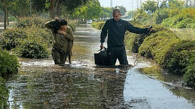 People try to wade through a flooded street after heavy rains in the southern Israeli city of Ashkelon on Nov. 9, 2015. Photo by Edi Israel/Flash90.