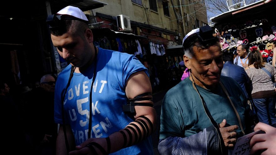 Israeli Jewish men put on tefillin at the entrance to Carmel Market in downtown Tel Aviv on Feb. 10, 2017. Photo by Tomer Neuberg/Flash90.