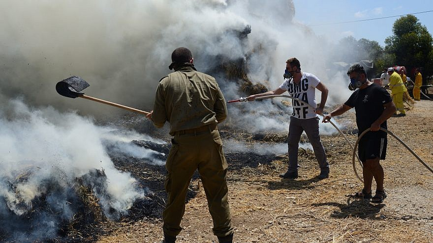 Firefighters and security teams put out a fire that broke up in a cowshed, caused by a kite loaded with an incendiary device launched from Gaza, in Nahal-Oz on July 21, 2018. Photo by Gili Yaari/Flash 90.