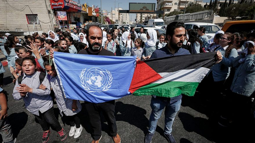 Palestinian protesters wave flags during a protest against the U.S. decision earlier this year to cut U.N. aid funds to Palestinians in Bethlehem, on Sept. 26, 2018. Photo by Wisam Hashlamoun/Flash90.