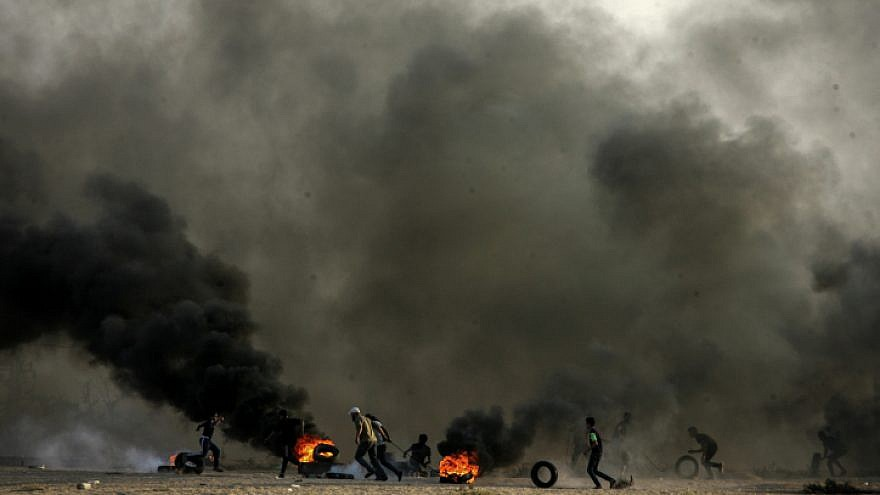 Palestinian demonstrators burn tires as part of a violent demonstration on the Gaza-Israel border that turned deadly on Oct. 12, 2018, when a Gaza exploded a bomb and infiltrated the security fence in the attempt to attack Israeli soldiers. Photo by Abed Rahim Khatib/Flash90.