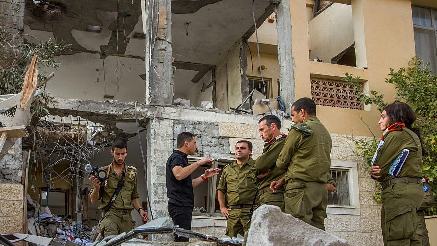 Maj.-Gen. Herzi Halevy (center), the chief of the Israeli Southern Command, visits the scene where a building was hit by a rocket fired by Hamas in Gaza in the southern Israeli city of Beersheva on Oct. 17, 2018. Photo by Flash90.