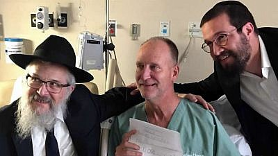 Officer Dan Mead, center, holds a letter of thanks from second-grade students at Yeshiva Schools of Pittsburgh. He is flanked by Rabbi Yisroel Rosenfeld, left, and Rabbi Henoch Rosenfeld. Credit: Chabad.org/News.