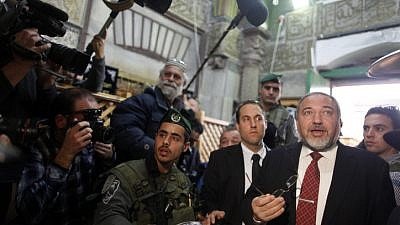 Israeli Defense Minister Avigdor Lieberman is seen surrounded by security as he visits the Tomb of the Patriarchs and Matriarchs in the city of Hebron on Jan. 14, 2013. Photo by Flash90.
