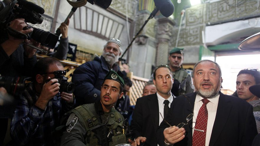 Israeli Defense Minister Avigdor Lieberman is seen surrounded by security as he visits the Tomb of the Patriarchs and Matriarchs in the city of Hebron on Jan. 14 2013