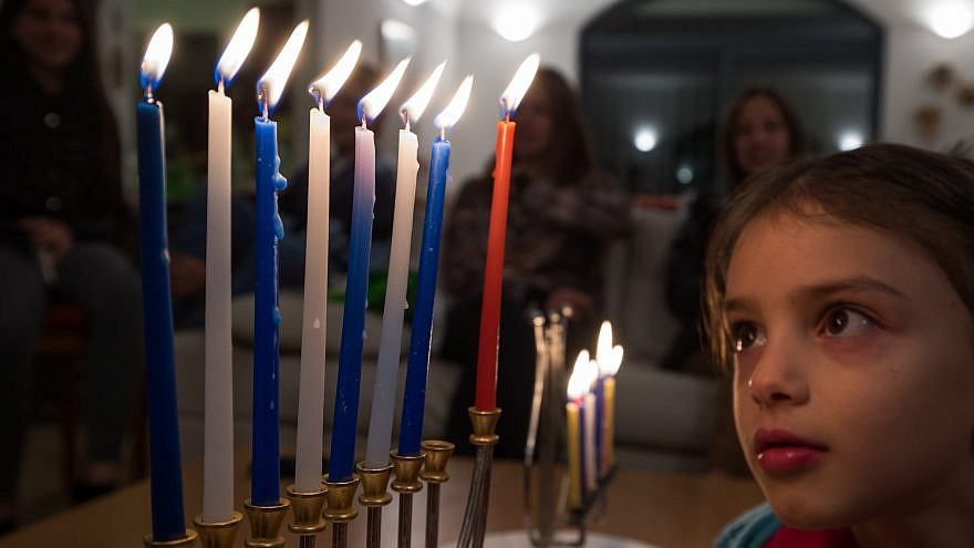 A child observes the candles on a fully lit Hanukkah menorah, Dec. 12, 2015. Photo by Nati Shohat/Flash90.