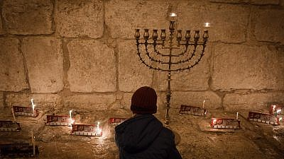 """Candles on the first night of the Jewish holiday of Hanukkah, in the Jerusalem neighborhood of Mea Shearim. Hanukkah, also known as the """"Festival of Lights,"""" is an eight-day Jewish holiday commemorating the rededication of the Holy Temple. The festival is observed by the kindling of the lights of a """"hanukkiyah,"""" a nine-branched candelabrum with one additional light being lit on each night of the holiday. Dec. 24, 2016. Photo by Sebi Berens/Flash90."""