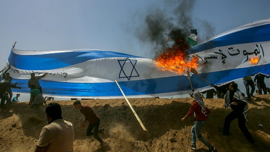 Palestinians protestors burn a a giant Israeli flag during clashes with Israeli security forces on the Gaza Israeli border east of Khan Yunis, in the southern Gaza Strip on April 6, 2018. Photo by Abed Rahim Khatib/Flash90.